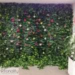 Ivy Mat Panel upholstered to a wall at a Funktionality event, decorated with artificial flowers.