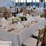 Wedding setting by Funktionality with white tables, florals and silver patterned votives.