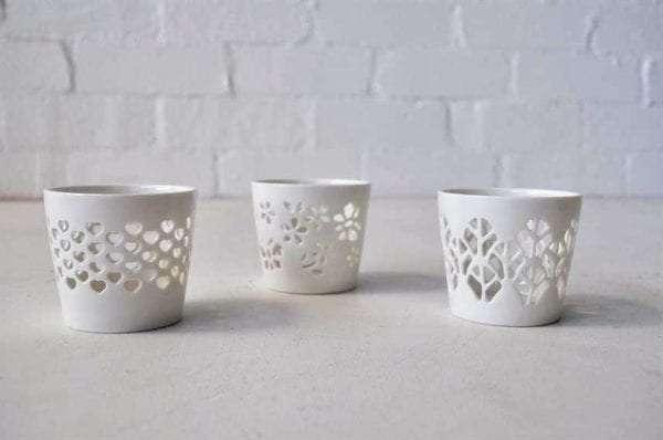 Set of three different white stencilled ceramic votives.