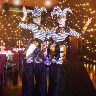 Harlequin Black and Gold Jester stilt walkers